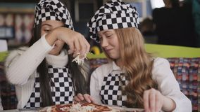 Cheerful girls in uniform cooking a pizza on master class of chief in cafe. 4K stock video footage