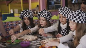 Cheerful girls in uniform cooking a pizza on master class of chief in cafe. 4K stock footage