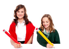 Cheerful girls writing with pencil on surface. Isolated against white background Stock Photo