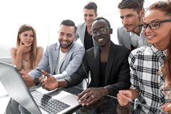 Cheerful glad joyful positive economists. Economists looking at screen of laptop, computer with wondered amazed expression, emotions in modern office royalty free stock photo