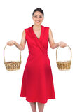 Cheerful glamorous model in red dress holding baskets Royalty Free Stock Image