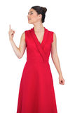 Cheerful glamorous model in red dress pointing up Stock Photography