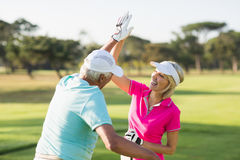 Cheerful golfer couple giving high five Royalty Free Stock Image
