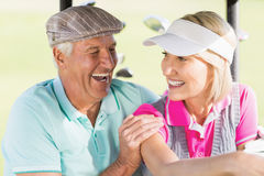 Cheerful golfer couple. Sitting in golf buggy Stock Photo