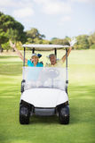Cheerful golfer couple sitting in golf buggy Stock Image