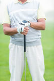 Cheerful golfer holding his club. On a foggy day at the golf course Royalty Free Stock Photography