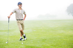 Cheerful golfer holding his club with hand on hip. At the golf course Stock Image
