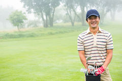 Cheerful golfer smiling at camera holding golf bag Stock Image