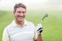 Cheerful golfer smiling at camera holding his club. On a foggy day at the golf course Stock Images