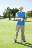 Cheerful golfer smiling at camera holding his club Stock Image