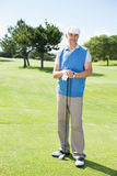 Cheerful golfer smiling at camera holding his club. On a sunny day at the golf course Stock Image