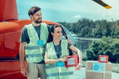 Cheerful good-looking hard-working volunteers being surrounded with boxes stock photo