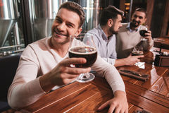 Cheerful good looking man taking pleasure in his drink. Time to relax. Cheerful good looking positive men raising his glass and smiling while taking pleasure in Stock Photos