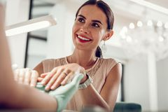 Cheerful good-looking woman wearing unusual jewelry while visiting salon royalty free stock photos