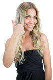 Cheerful gorgeous blonde in black dress thumbs up Stock Image