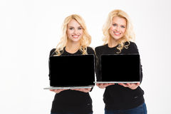 Cheerful gorgeous blonde sister twin holding blank laptop computer screen. Cheerful gorgeous blonde sisters twins holding blank laptop computer screen isolated Royalty Free Stock Images