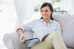 Cheerful gorgeous brunette reading magazine Royalty Free Stock Image