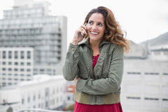 Cheerful gorgeous brunette in winter fashion using smartphone Royalty Free Stock Images