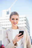 Cheerful gorgeous businesswoman sending a text message Royalty Free Stock Photos