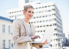 Cheerful gorgeous businesswoman working on laptop Stock Photography