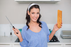 Cheerful gorgeous model holding knife and bread Royalty Free Stock Photography