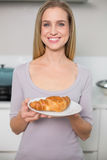 Cheerful gorgeous model holding plate with croissant Stock Image