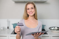 Cheerful gorgeous model holding tablet and credit card Royalty Free Stock Images