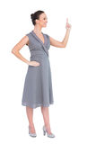 Cheerful gorgeous woman in classy dress pointing her finger up Stock Photography