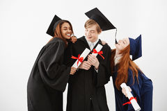 Cheerful graduate classmates celebrating smiling rejoicing over white background. Cheerful graduate classmates with diplomas celebrating smiling rejoicing over Royalty Free Stock Photography