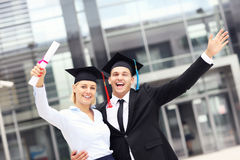Cheerful graduates outside university Stock Photography