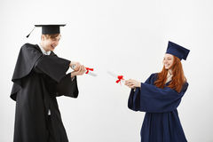 Cheerful graduates smiling fighting with diplomas over white background. Cheerful graduates in caps and mantles smiling fighting with diplomas over white Royalty Free Stock Photography