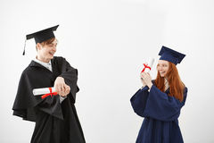 Cheerful graduates smiling fighting with diplomas over white background. Cheerful graduates in caps and mantles smiling fighting with diplomas over white Stock Photo