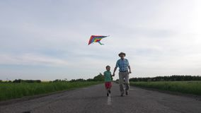 Joyful grandpa with grandson flying kite outdoor