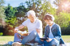 Cheerful grandfather spending weekend with grandson outdoors royalty free stock image
