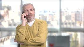 Cheerful grandfather talking on mobile phone. stock footage