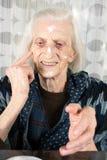Cheerful grandma applying face cream Stock Image