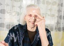 Cheerful grandma applying face cream Stock Photo