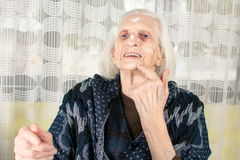 Cheerful grandma applying face cream. At home Royalty Free Stock Image