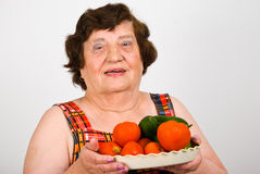 Cheerful grandma holding fresh vegetables Stock Images