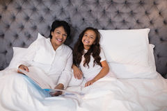Cheerful grandmother and granddaughter resting on bed at home Royalty Free Stock Image