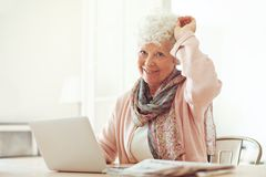 Cheerful Grandmother at Home with Laptop Stock Images