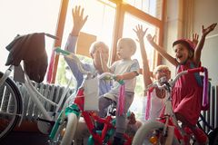 Cheerful grandparents buying new bicycle for little grandchildren. Cheerful grandparents buying new bicycle for happy little grandchildren royalty free stock photos