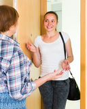 Cheerful greeting of two women at the door Royalty Free Stock Images