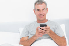 Cheerful grey haired man sending a text in bed Stock Photos