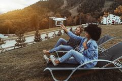Cheerful grils on deck chairs are holding flying quadcopter. Two beautiful laughing girls the black one and Caucasian one are holding flying drone which is Royalty Free Stock Photo