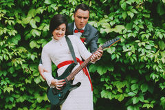 Cheerful groom and bride playing the guitar Royalty Free Stock Photo