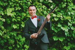 Cheerful groom playing the guitar Stock Photography