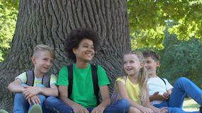 Cheerful group of children joking laughing together sitting park under tree