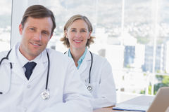 Cheerful group of doctors posing at their desk. In their office Royalty Free Stock Photos