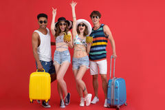 Cheerful group of friends holding suitcases and cocktails. Stock Images